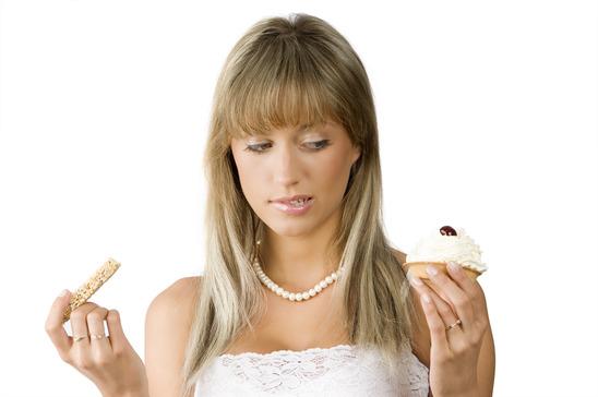 beautiful girl in hesitation to choose between sweet or diet food